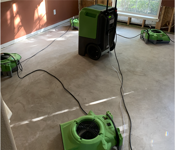 Air movers and dehumidifier set up on the floor of an empty bedroom.