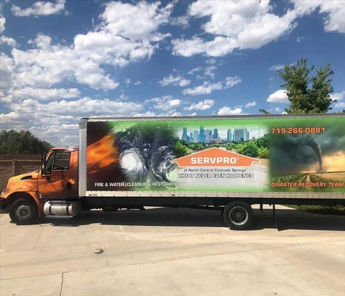 A large semi truck branded with SERVPRO logo and storm pictures