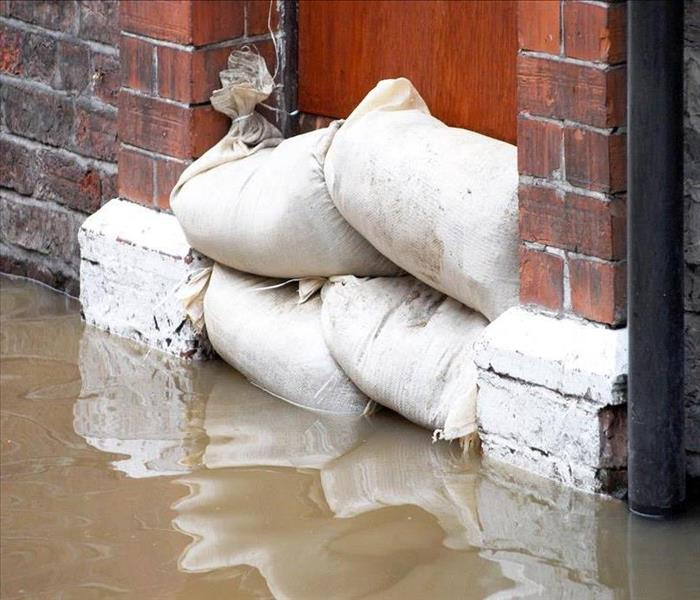 Image of sandbags placed on door to block water from entering a building.