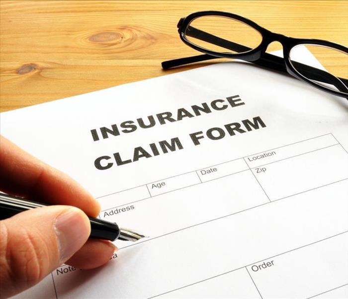 Image of an insurance claim form and a hand filling in the form.