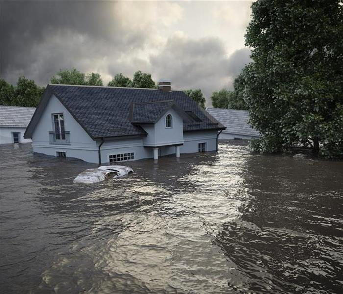 Image of a flooded neighborhood. A house is underwater.